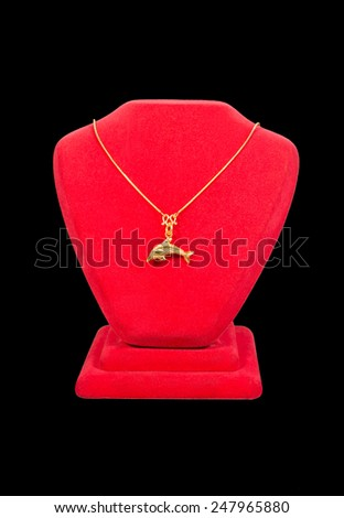 golden necklace and dolphin locket on red stand isolated on black