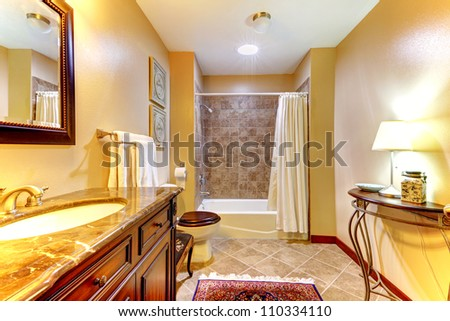 Golden nice bathroom with brown  ceramic tiles and wood cabinet. - stock photo
