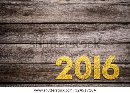 Golden number with 2016 on wooden table background, new year template - stock photo