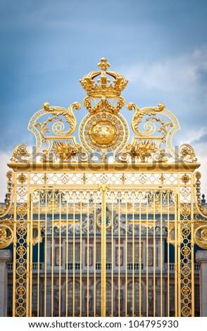 Golden ornate gate of Chateau de Versailles with blue sky and clouds in background. Paris, France, Europe. - stock photo