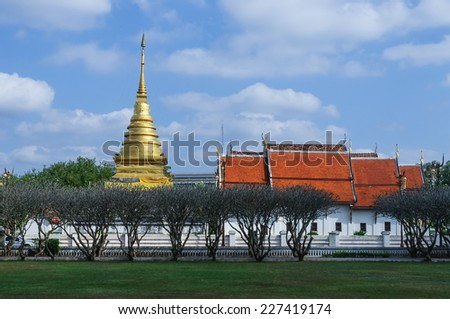 Golden pagoda  and Buddhist sanctuary of  Changkam temple  in Nan Province, Thailand, which leafless pagoda or temple trees are in the foreground - stock photo