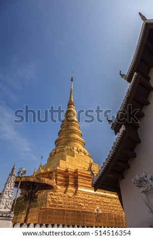 golden pagoda and lion statue in front the sanctuary, Nan, northern of Thailand,