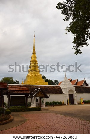 golden pagoda  in temple at Nan, northern of Thailand, white sky, cloudy   - stock photo