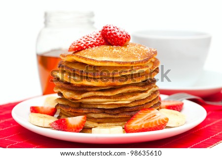 golden pancakes pancakes with honey and cup of tea - stock photo