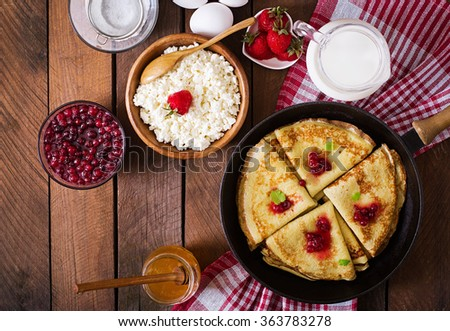 Golden pancakes with cranberry jam and honey in a rustic style. Top view - stock photo