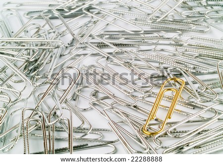 Golden Paperclip on a bunch of Silver 3 - stock photo