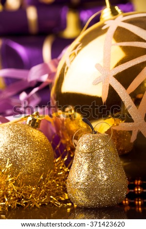 golden pear,matte surface gold ball and big gold ball with snowflake, gold tinsel against violet or purple xmas gift boxes