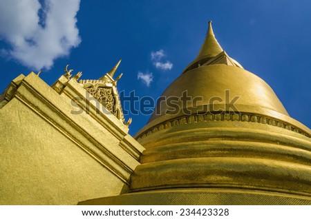 Golden Phra Si Rattana Chedi and Phra Mondop against blue sky in Emerald Buddha Temple (Wat Phra Kaew), Grand Palace Complex, symbol of Thailand, Bangkok, Thailand   - stock photo
