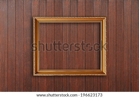 Golden picture frame on wooden wall
