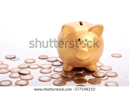 Golden piggy bank with savings in coins on white background - stock photo
