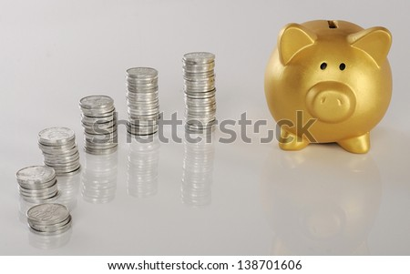 Golden piggy bank with stack of coins