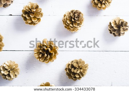 golden pine cones Christmas decoration on white wood table background - stock photo