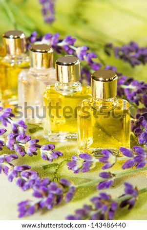 Golden plant extracts and essential oils in clear glass bottles for use in aromatherapy and perfumery surrounded by fresh purple blossom - stock photo