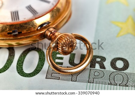 golden pocket watch and euro bills, extra close up - stock photo