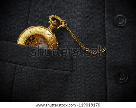 Golden pocket watch in pocket of black men's waistcoat. Low-key image. - stock photo