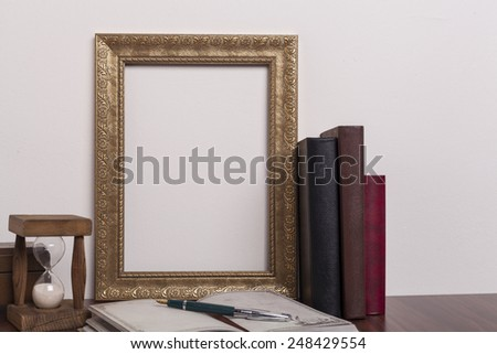 Golden portrait frame with books and hourglass on wood table - stock photo
