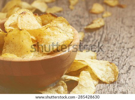 Golden potato chips in a wooden bowl on the old table, selective focus - stock photo