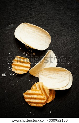 Golden potato chips with salt on black stone background, top view - stock photo