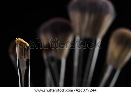 Golden powdering on the top of the brush. The best variant for make-up while clubbing or going out. Blurred background with brushes for applying foundation. - stock photo