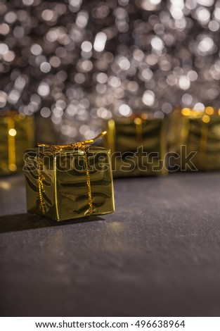 Golden present box, gift package, with shallow depth of field in front of dark glitter bokeh background