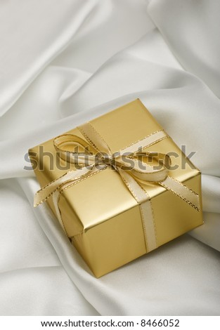 golden present with a note on silver silk close up - stock photo