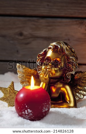 Golden putto with burning candle and star shaped christmas decorations on pile of snow - stock photo