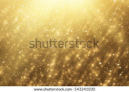 Golden rays and sparkles or glitter lights. Merry Christmas festive gold background.defocused circle bokeh or particles