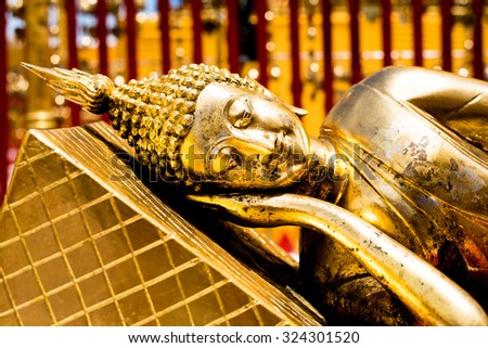 Golden reclining Buddha statue in public temple - stock photo