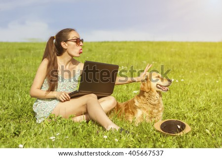 golden retriever, attractive girl with a laptop, business girl with her pet on the grass, green grass sun (shallow dof)