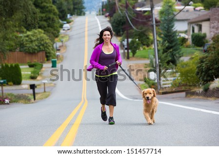 Golden Retriever dog running with a pretty woman - stock photo