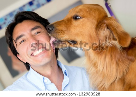 Golden retriever licking his owner in the face as a sign of affection - stock photo