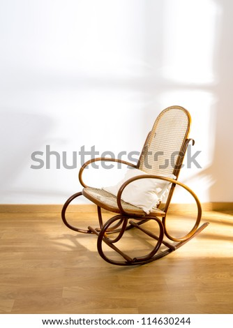 Golden retro rocker wooden swing chair on wood floor as a vintage memories - stock photo