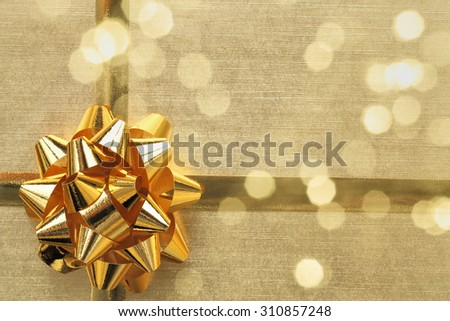 Golden ribbon bow with bokeh,Holiday decoration. - stock photo
