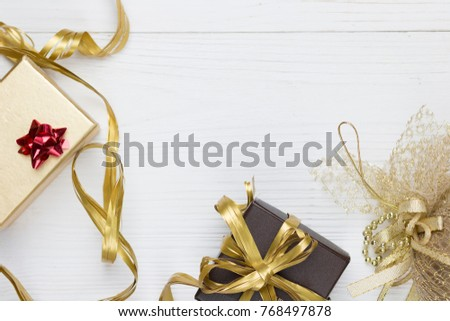 golden ribbon, golden box, gold decoration, hristmas background with decorations gift box with snowflake Merry Christmas and Happy New Year text on white table.