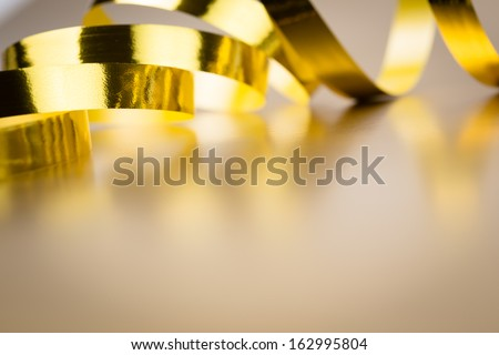 Golden ribbon on golden background - stock photo