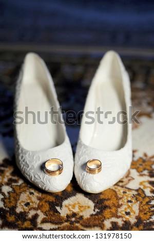golden rings on white wedding shoes on carpet - stock photo