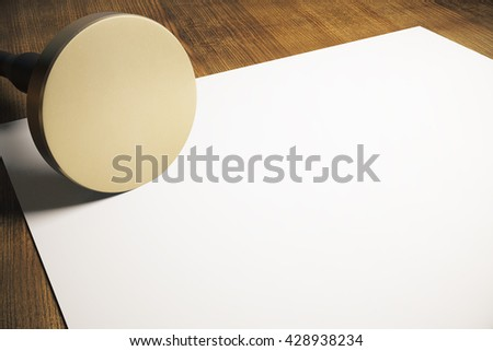 Golden round stamper and blank paper sheet on wooden background. Mock up, 3D Rendering - stock photo