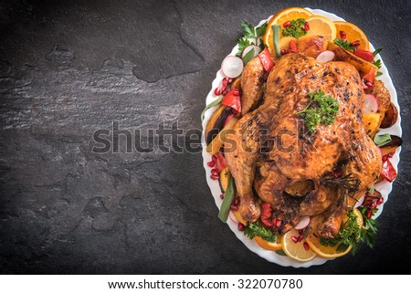 Golden rustic and stuffed roast turkey with vegetables on dark background,selective focus and blank space - stock photo