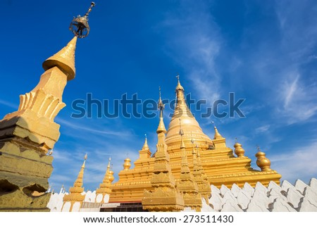 Golden Sandamuni Pagoda with row of white pagodas. Amazing architecture of Buddhist Temples at Mandalay. Myanmar (Burma) travel landscapes and destinations - stock photo
