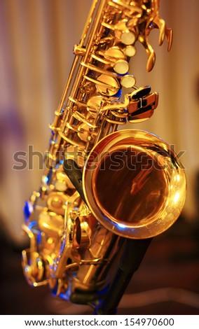 Golden saxophone musical instrument detail - stock photo