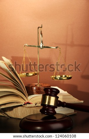 Golden scales of justice, gavel and books on brown background - stock photo