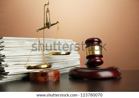 Golden scales of justice, gavel and folders on brown background - stock photo