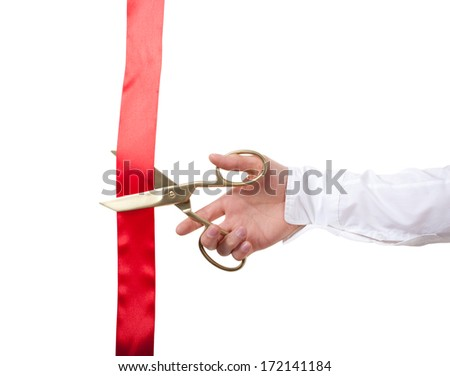 Golden scissors cutting a red ribbon, isolated on a white background. - stock photo