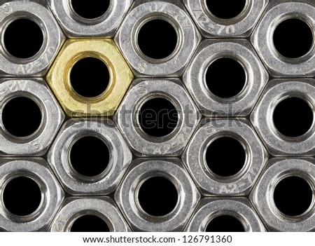 Golden screw nut in steel nuts pattern isolated on black. Abstract background.  - stock photo