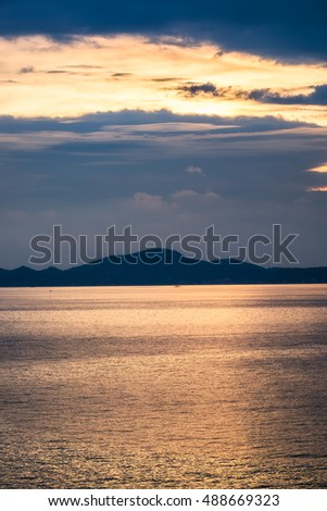 Golden sea with island at sunset