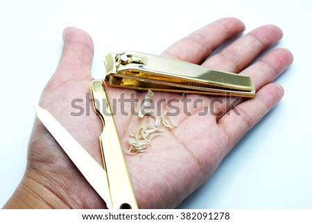 Golden set of steel nail clipper/manicure set with nails in female hand on white-blue background.  - stock photo