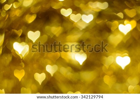 Golden shiny hearts bokeh, festive background - stock photo