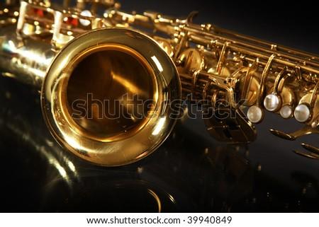golden shiny saxophone on black background - stock photo