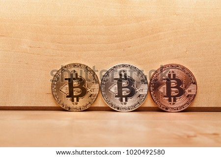 Golden, Silver and Copper Bitcoins on wood