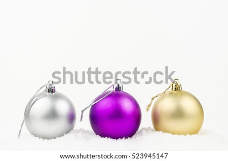 Golden, silver and purple Christmas balls with snow isolated on white background